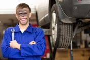Portrait of a happy young car mechanic holding wrench with car on hoist in background. Horizontal shot.
